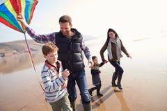 Famille courant le long du cerf-volant de vol de plage d'hiver Photos libres de droits