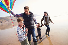 Famille courant le long du cerf-volant de vol de plage d'hiver Images stock
