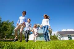 Famille courant sur la pelouse près de la maison Photo stock