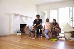 Famille déballant des boîtes dans la nouvelle maison le jour mobile photo libre de droits