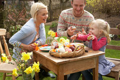 Famille décorant des oeufs de pâques sur le Tableau à l'extérieur image stock