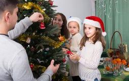 Famille décorant l'arbre de Noël à la maison Images libres de droits