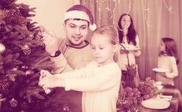 Famille décorant l'arbre de Noël à la maison Photo stock