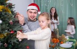 Famille décorant l'arbre de Noël à la maison Photos libres de droits