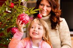 Famille décorant l'arbre de Noël Image stock