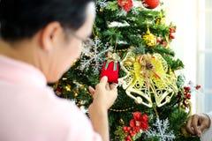 Famille décorant un arbre de Noël et père donnant Noël G image stock