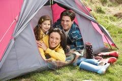 Famille détendant à l'intérieur de la tente des vacances campantes Photographie stock