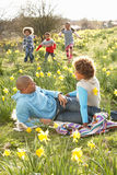 Famille détendant dans le domaine des jonquilles de source images stock