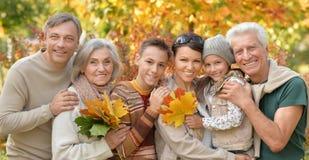 Famille détendant en parc d'automne Photo stock