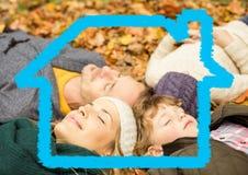 Famille détendant sur les feuilles sèches avec le modèle de maison images libres de droits