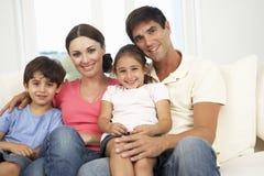 Famille détendant sur Sofa At Home Together Image libre de droits