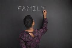 Famille d'écriture de professeur de femme d'afro-américain sur le fond de conseil de noir de craie Images stock