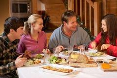 Famille d'adolescent appréciant le repas dans le chalet alpestre Images stock