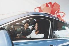 Famille d'afro-américain au concessionnaire automobile La mère et le fils s'asseyent dans la nouvelle voiture Images libres de droits