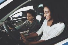 Famille d'afro-américain au concessionnaire automobile La mère et le fils s'asseyent dans la nouvelle voiture Photographie stock libre de droits