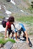 Famille d'alpinistes trimardant dans les montagnes Photographie stock