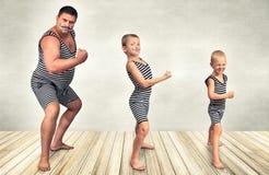 Famille d'homme fort Le père de deux fils dans le costume de vintage des athlètes exécutent des exercices de force Regard de fami photos stock