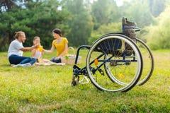 Famille d'un jus potable d'homme handicapé sur le pique-nique Photographie stock libre de droits