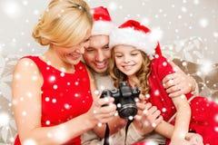 Famille dans des chapeaux d'aide de Santa regardant des pictires Images libres de droits