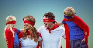 Famille dans des costumes de super héros sur le fond bleu Photos stock