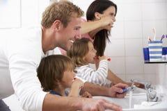 Famille dans des dents de brossage de salle de bains Photos stock