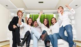 Famille dans l'intérieur moderne regardant une rencontre de gain Images stock