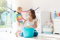 Famille dans la buanderie avec la machine ? laver image stock