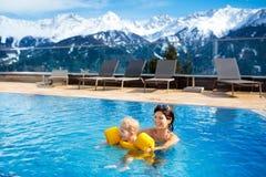 Famille dans la piscine extérieure de la station thermale alpine Image stock