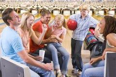 Famille dans la ruelle de bowling avec encourager de deux amis Image stock
