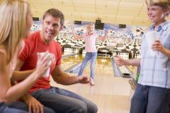 Famille dans la ruelle de bowling encourageant et souriant Photographie stock