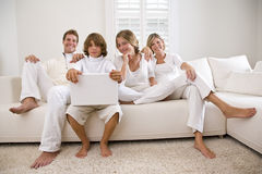 Famille dans le blanc sur le sofa blanc photos libres de droits