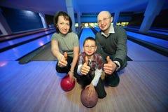 Famille dans le club de bowling et des mains d'expositions d'ok Photographie stock