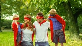 Famille dans le costume de super héros en parc Photo libre de droits