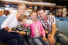 Famille dans le salon de départ d'aéroport attendant pour partir en vacances Photographie stock libre de droits