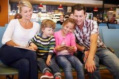 Famille dans le salon de départ d'aéroport attendant pour partir en vacances Images stock