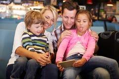Famille dans le salon de départ d'aéroport attendant pour partir en vacances Photo stock
