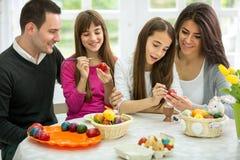 Famille décorant des oeufs de pâques ensemble Image stock