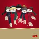 Famille de bonhomme de neige sur le fond rouge Photographie stock libre de droits