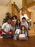 Famille de chemin mélangé permutant des cadeaux à Noël images stock