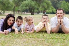 Famille de cinq gaie se trouvant sur la pelouse Photographie stock libre de droits