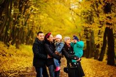 Famille de marche avec deux enfants en parc automnal Image libre de droits