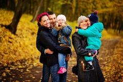 Famille de marche avec deux enfants en parc automnal Images libres de droits