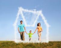 Famille de marche avec la maison de nuage de garçon et de rêve Photo stock