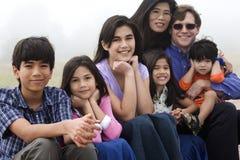 Famille de Mutiracial s'asseyant sur la plage Images libres de droits