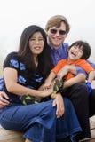 Famille de Mutiracial s'asseyant sur la plage Image libre de droits