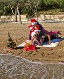 Famille de Noël s'étendant sur la plage de sable Photos stock