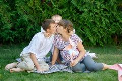 Famille de père et garçon de mère, parent embrassant à l'un l'autre et petit garçon souriant et étreignant Images stock