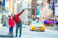 Famille de père et de peu d'enfant sur le Times Square pendant leurs vacances à New York City Photo libre de droits