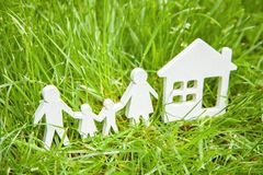 Famille de père, de mère, de fils et de fille près de la maison sur l'herbe Le concept est maison écologiquement propre pour la f Photo stock