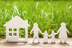 Famille de père, de mère, de fils et de fille près de la maison sur l'herbe verte Le concept est maison écologiquement propre pou Image stock